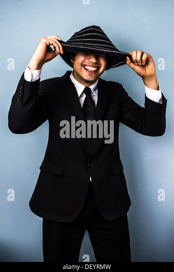 Young business man is smiling from under his woolen hat - Stock Image