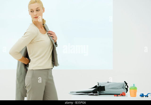 Professional woman dressing, looking over shoulder, sippy cup and toys next to bag - Stock-Bilder