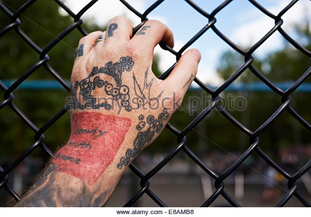 Male tattooed hand holding onto park wire fence - Stock Image