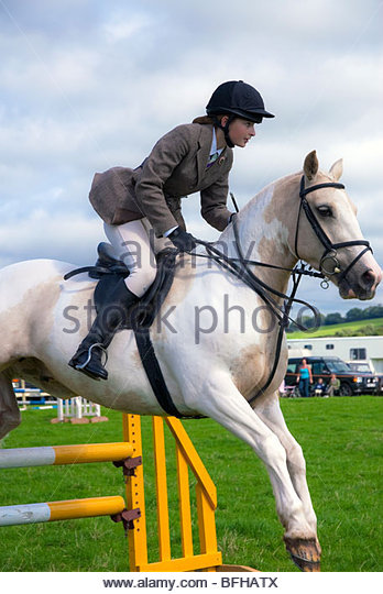 British show jumping competition at Lea Show near Ross on Wye,UK. Teenage girl on a horse show jumping at local - Stock Image