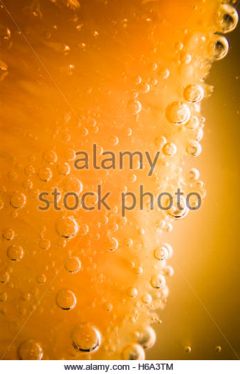 Close photo on a underwater sliced orange with water bubble details. Tequila sunrise background - Stock Image