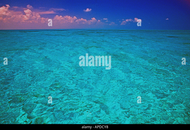 tropics tropical water crystal clear clean turquoise romantic romance pink clouds - Stock Image