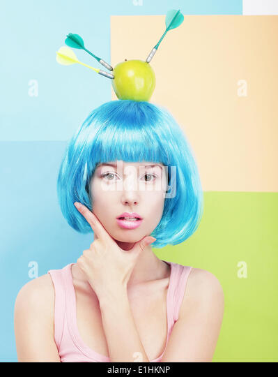 Creativity. Woman with Painted Blue Hairs and Apple on her Head - Stock Image