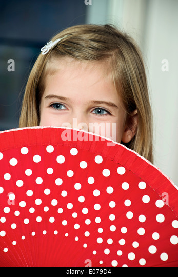 Girl holding red fan with white dots - Stock Image