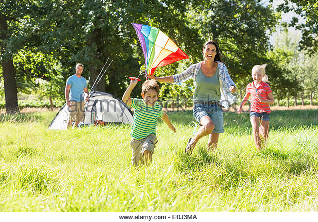 Family Flying Kite Camping Holiday In Countryside - Stock-Bilder
