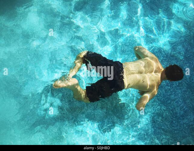 Teenager boy swimming underwater in outdoor swimming pool. - Stock Image