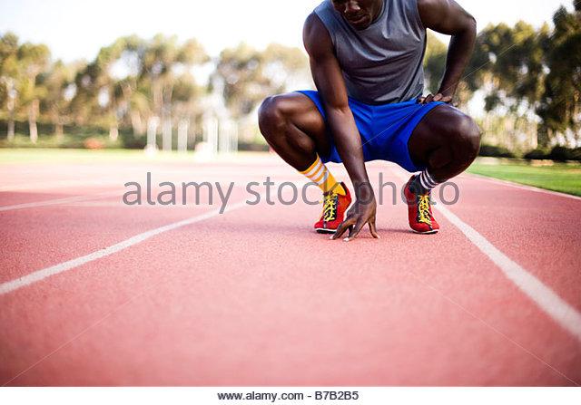 African American runner squatting on track - Stock-Bilder