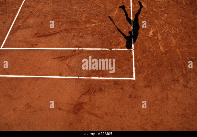 The shadow of a tennis player serving during a game on a clay court - Stock Image