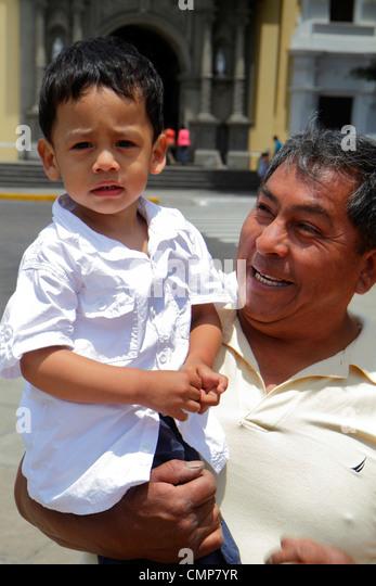Lima Peru Barranco District Parque Municipal urban park outdoor space Hispanic man boy toddler carrying holding - Stock Image