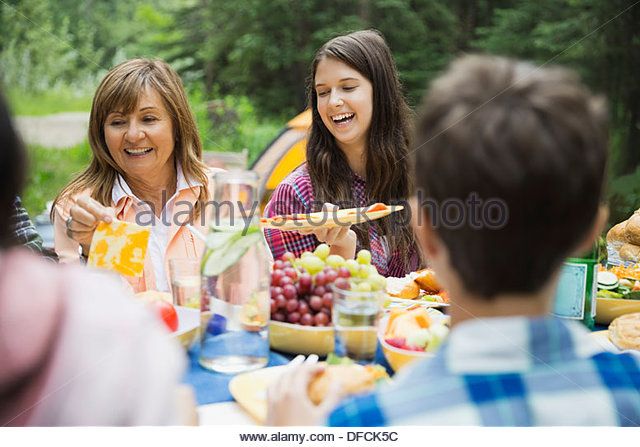 Happy family having meal at campsite - Stock Image
