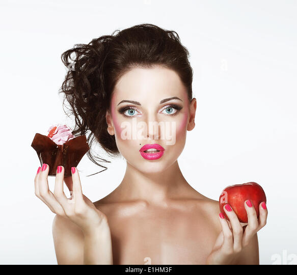Dilemma. Diet. Undecided Woman with Apple and Cupcake - Stock Image