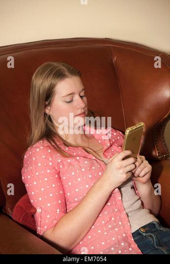 Teenage girl using iPhone mobile phone device indoors  MR  © Myrleen Pearson - Stock-Bilder