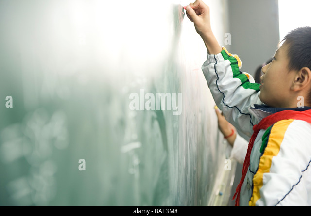 A young student writing on a chalkboard. - Stock Image