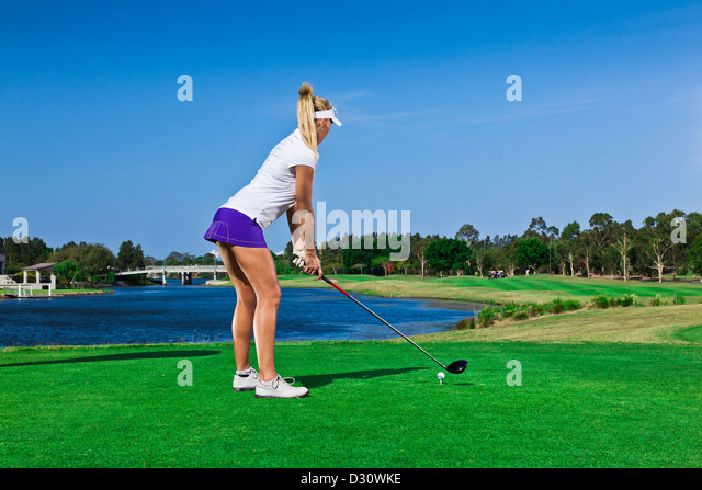 Attractive golfer girl on golf course with driver - Stock Image