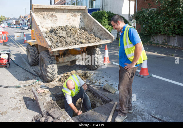Road workers digging hole on street, St.Jude's Road, Englefield Green, Surrey, England, United Kingdom - Stock Image