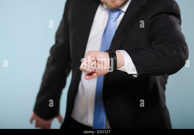 Businessman in hurry watching his clock. Middle section of casually suited man moving and checking time from his - Stock Image