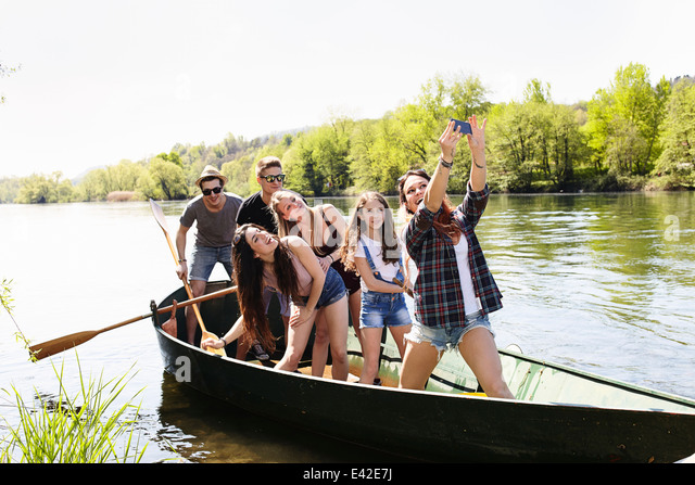 Group of friends in a row boat taking photo of themselves - Stock Image