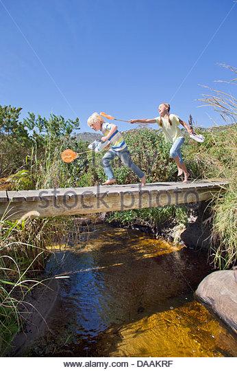 Girl chasing boy with fishing net on footbridge over stream - Stock Image