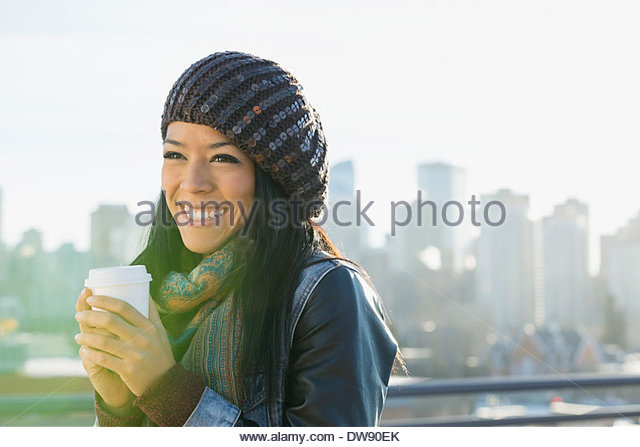 Woman holding disposable coffee cup outdoors - Stock-Bilder