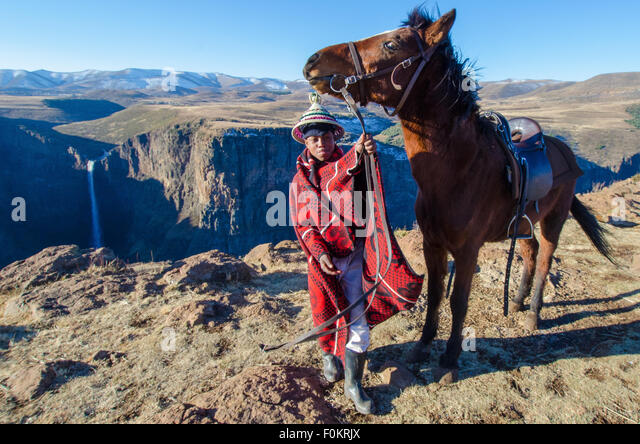 A young shepherd guides his horse along the cliffs of Lesotho near Maletsunyane Falls. - Stock Image