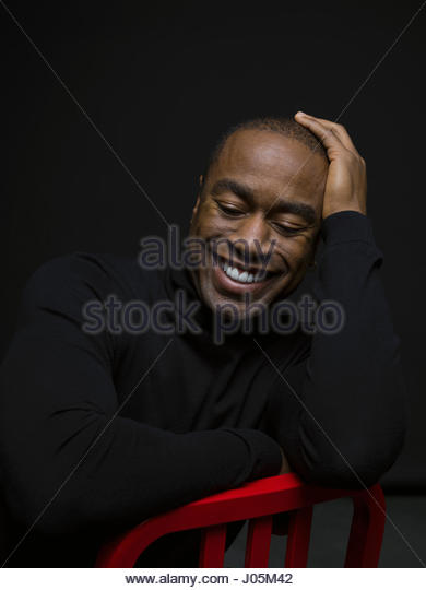 Portrait smiling African American man looking down with head in hand against black background - Stock Image