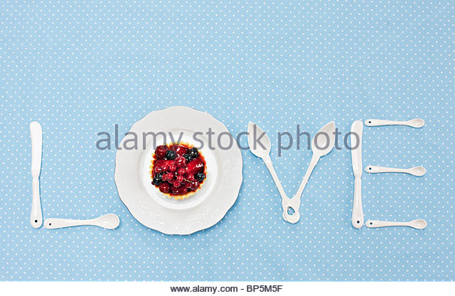 Silverware and plate with tart spelling 'love' on tablecloth - Stock-Bilder