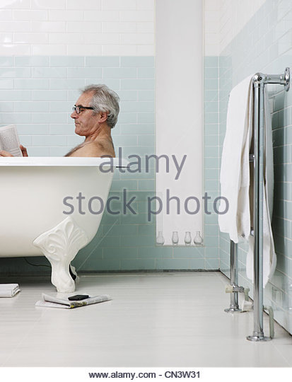 Senior man bathing and reading book - Stock Image