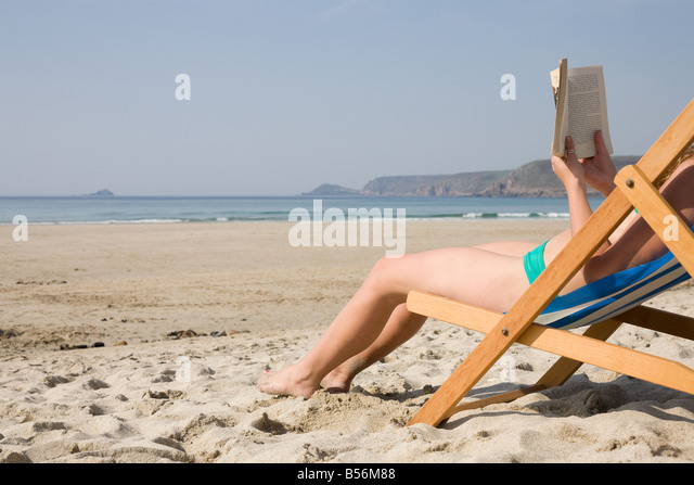 Woman reading a book on an empty beach - Stock Image
