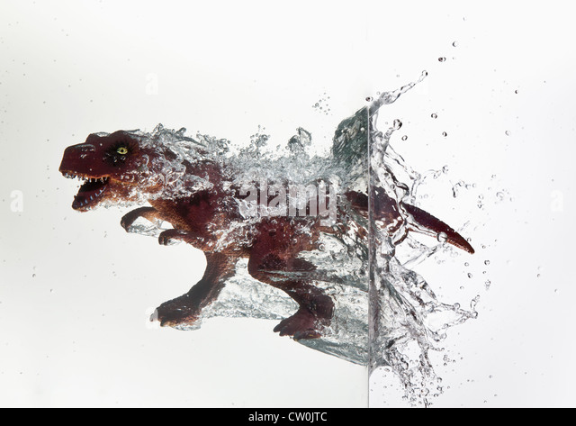 Toy dinosaur plunging into water - Stock Image