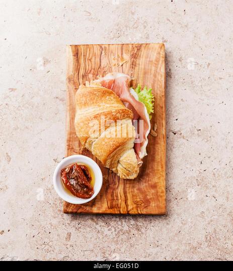 Ham croissant sandwich on stone textured background - Stock Image