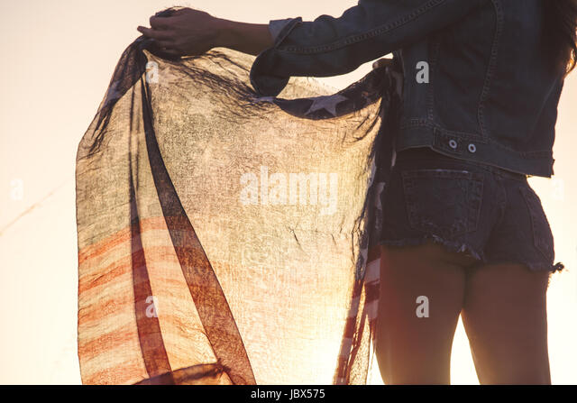 Woman wearing denim shorts, holding American flag, mid section, rear view - Stock-Bilder
