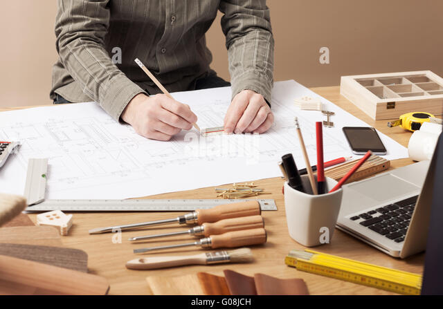 Professional architect and construction engineer working at office desk hands close-up, he is drawing on a building - Stock Image