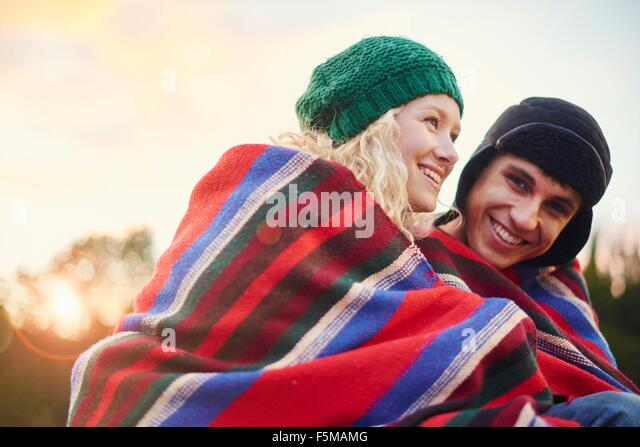 Portrait of romantic young camping couple wrapped in blanket - Stock-Bilder