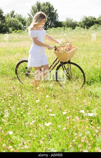 MODEL RELEASED. Young woman in meadow with bicycle. - Stock-Bilder