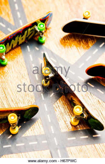 Creative sport photo on tipped skateboarder deck laying sideways on transport highway links. Side streets of skate - Stock Image