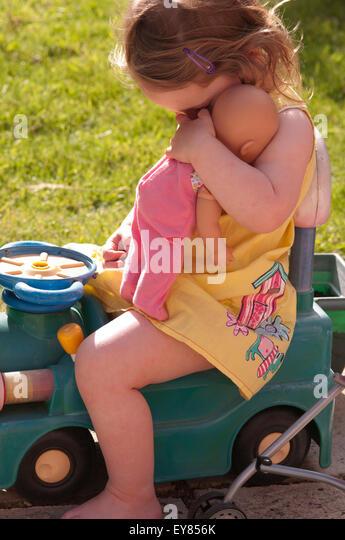 Shy little girl hugging her doll - Stock Image
