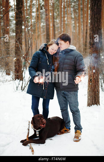 Happy Couple with Dog Labrador Retriever Enjoying Winter Evening with Festive Sparklers for Christmas Time - Stock Image