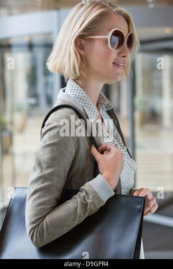 Woman carrying a handbag - Stock Image