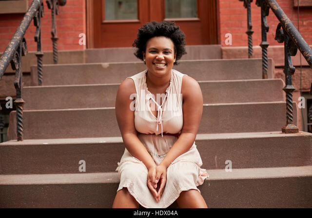 Portrait of smiling Black woman sitting on urban front stoop - Stock Image
