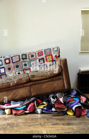 Pile of shoes by leather sofa - Stock Image