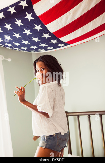 Young woman holding rose with US flag - Stock Image