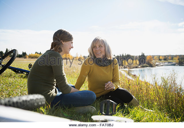 Grandmother and granddaughter resting near bicycles in sunny field - Stock Image