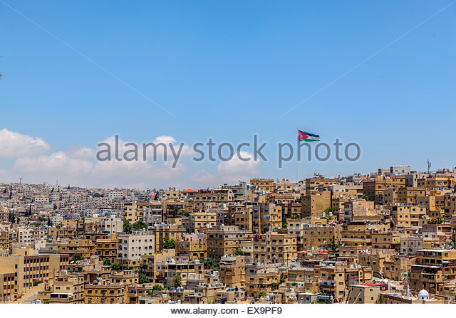 close-up view of Cityscape of downtown Amman, Jordan. Old buildings and Jordanian Flag, under partly cloudy sky. - Stock Image