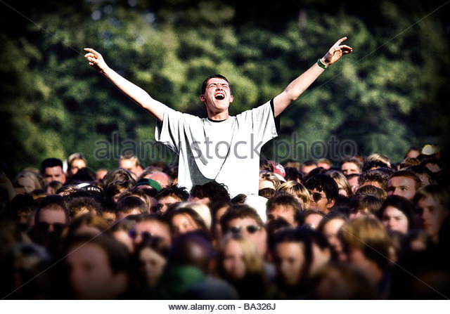 A crowd scene at a music festival with one male fan sat elevated above the crowd with arms raised. - Stock Image