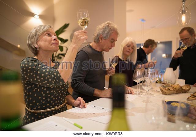 Senior woman eyeing and rating white wine,enjoying wine tasting party social gathering - Stock Image