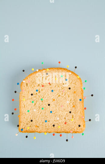 still life photography of a quirky soft bread stacked and used as a voodoo doll on a blue and minimal background - Stock Image