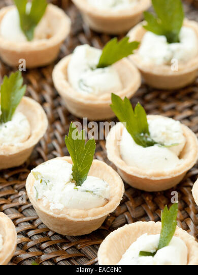 detail of goat cheese hors d'oeuvres with cilantro leaf - Stock Image