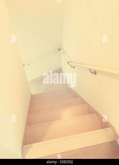 Simple, narrow staircase with light brown wood, white walls and handrail. Vintage paper texture overlay. - Stock Image
