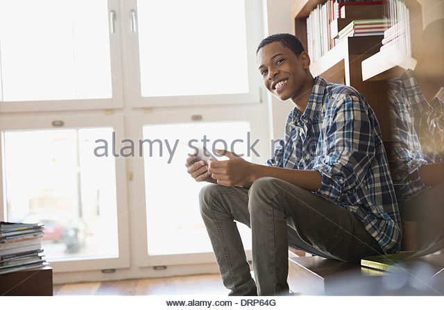 Smiling teen with digital tablet at home - Stock Image