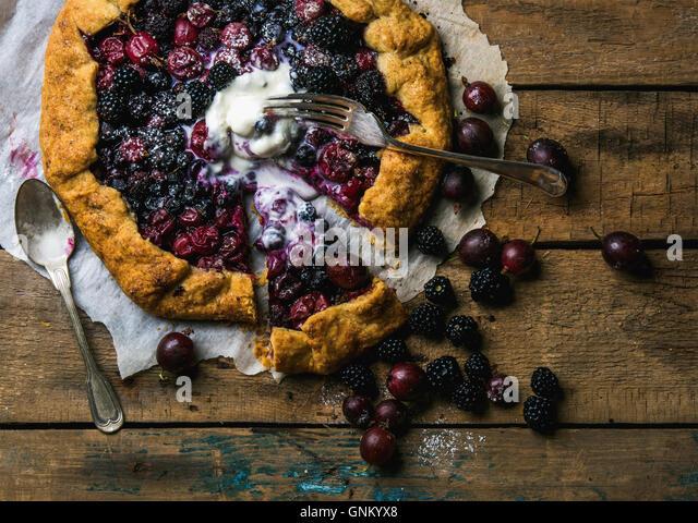 Garden berry crostata sweet pie with melted vanilla ice-cream scoop - Stock Image